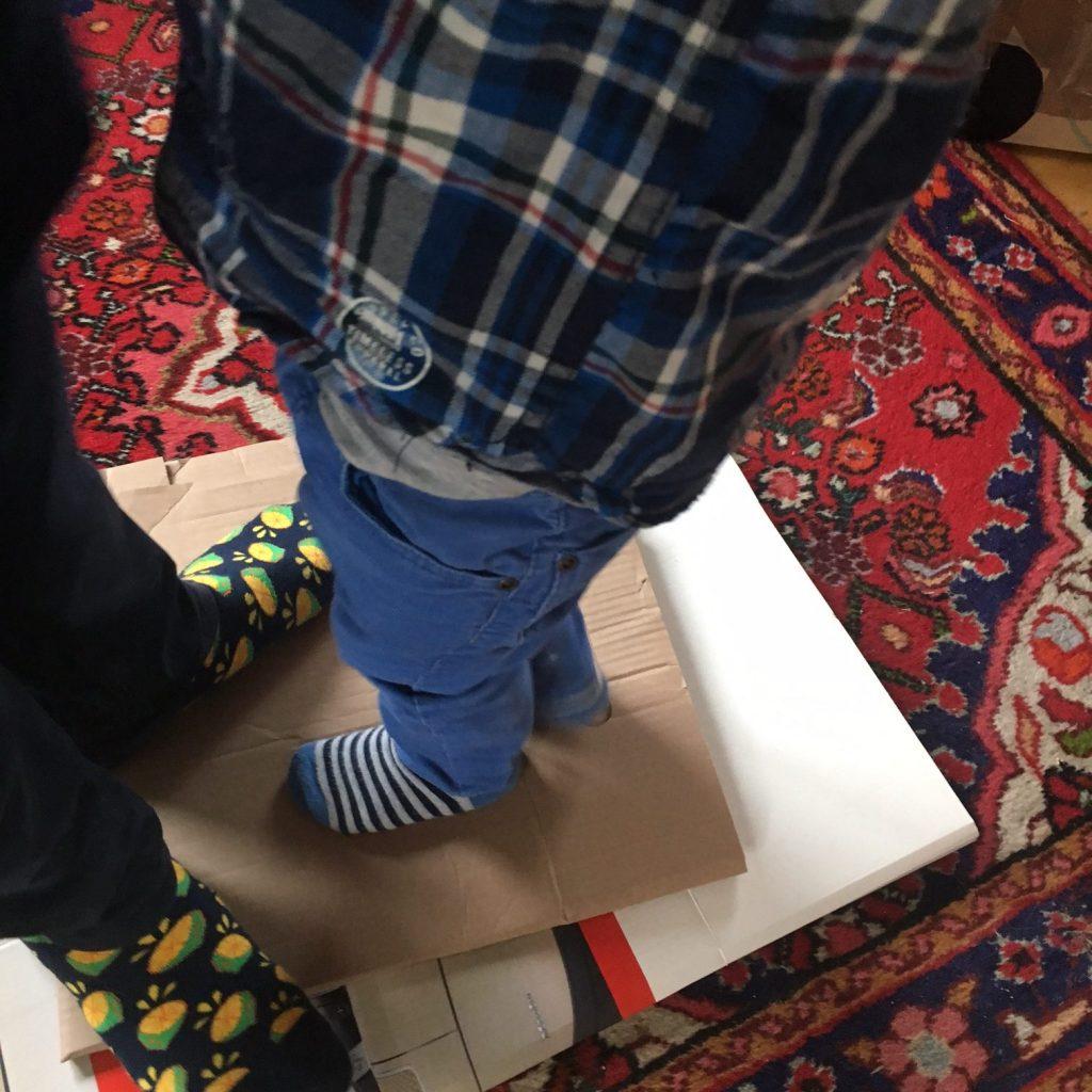 Vater und Sohn zerstampfen Kartons